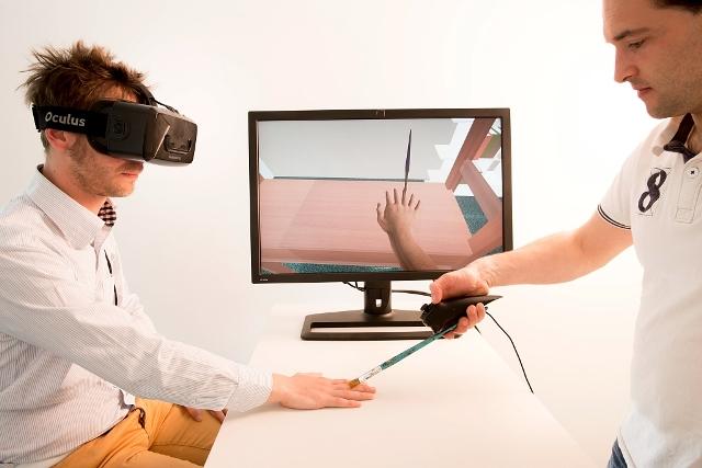 Six Fingers est une plateforme expérimentale de réalité virtuelle sur l'incarnation virtuelle (virtual embodiement) et l'avatar, développée par les équipes HYBRID et MIMETIC. L'utilisateur, équipé d'un visiocasque de réalité virtuelle, peut observer son corps virtuel (son avatar), et notamment ses mains (virtuelles). Ici a été généré l'illusion de la présence d'un 6e doigt sur la main droite, pour étudier comment cette main est assimilée par l'utilisateur comme si c'était la sienne. La plateforme comporte un visiocasque et un ordinateur pour faire tourner la simulation de réalité virtuelle. Pour favoriser la « transition » entre environnements réels et virtuels, des éléments « tangibles » sont présents dans les deux mondes : l'étagère en bois que l'utilisateur peut toucher est reproduite à l'identique dans la scène virtuelle. L'expérience propose de faire « ressentir » ce 6e doigt. Le doigt supplémentaire a été introduit entre l'annulaire et le petit doigt, et son mouvement interpolé à partir des deux doigts environnants : dès que l'utilisateur ferme l'annulaire et/ou le petit doigt, le 6e doigt se referme également. Pour faire « ressentir » ce 6e doigt, un expérimentateur brosse successivement les doigts. Le pinceau et ses mouvements sont reproduits dans la scène virtuelle : le pinceau virtuel passe bien sur le 6e doigt, mais dans la réalité l'expérimentateur brosse de manière synchronisée l'annulaire. Crédits : J.C. Moschetti / INRIA