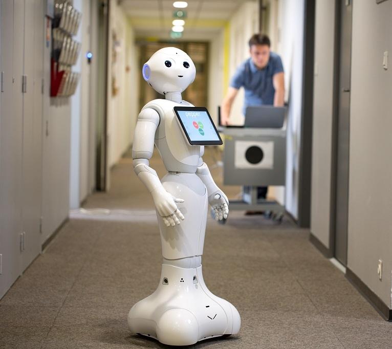 Fabien Spindler, ingénieur de recherche de l'équipe-projet Lagadic travaille avec le robot Pepper. Lagadic travaille sur l'asservissement visuel, i.e. le contrôle par la vue de machines équipées de moteur. Les robots (qu'ils soient drones, robots industriels, robots humanoïdes, voitures, etc.) «voient» grâce à des capteurs; ces capteurs sont le plus souvent des caméras, mais peuvent aussi être des échographes. L'asservissement peut aussi être basé sur le son; dans ce cas, les capteurs sont des micros. Pepper est un robot humanoïde. Il a une vingtaine de moteurs: six dans chaque bras, un au genou, deux à la hanche, un à la base du cou, un à la base de la tête. Peppera plusieurs capteurs: - un micro dans chaque oreille, - une caméra sur le front, une autre dans la bouche et des Kinect dans les yeux; les Kinect sont des caméras avec récepteurs infrarouges pour mesurer la distance vis à vis des personnes ou des obstacles en face de lui. - des capteurs tactiles sur le dessus de la tête. Les images repérées par les capteurs sont envoyées sur l'ordinateur qui les traite; le résultat de ce traitement permet de piloter le robot, notamment pour lui permettre de réaliser des actions. Il peut se déplacer dans tous les sens/directions (avant, côté, arrière). La main de Pepper peut juste tourner autour du poignet. Lagadic s'intéresse à la préhension (le fait de saisir un objet) ce qui est compliqué vu que ce robot ne peut pas bouger son poignet comme un humain. Pepper est polyglotte. Si on tape un texte, il le récite en bougeant les bras- mouvements programmés aléatoirement, mais on peut donner dans le texte des ordres comme «lève les bras» pour avoir un mouvement précis à un moment donné du discours. Credit : Inria