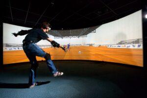 """Entraînement virtuel pour l'amélioration des performances sportives. Enregistrement et analyse des mouvements d'un gardien de but de handball, face à un joueur virtuel 3D. Le gardien est muni de capteurs de mouvements, et de lunettes pour voir son adversaire numérique. Le joueur virtuel est """"autonome"""" et décide seul de son jeu. Salle de réalité virtuelle immersive de l'INRIA Rennes - IRISA . Recherche menée en collaboration le Laboratoire Mouvement Sport Sabté (M2S) de l'université de Rennes 2. Photo Credit : INRIA / C. Lebedinsky"""